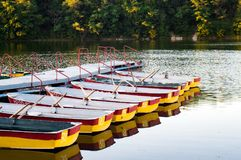 Pleasure rowing boats moored at the pier. stock photos