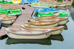 Pleasure rowing boats and pedalos tied up on a lake. With numerals painted on the boats royalty free stock image
