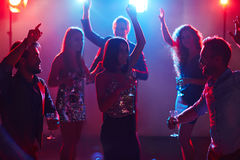 Pleasure-seekers having fun. Young beautiful people hanging out in popular night club, dancing with hands up and smiling cheerfully Stock Photos