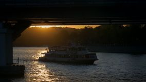 The pleasure ship floats under the bridge. Under the rays of the setting sun stock video