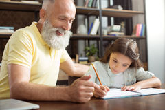 Smiling grandfather helping his granddaughter with homework. Pleasure to help. Charming elderly men sitting next to his pretty little granddaughter doing her Royalty Free Stock Photos