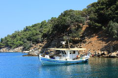 Pleasure to sail!. Boat moored on the shore of the Aegean Sea on a deserted island Royalty Free Stock Photos