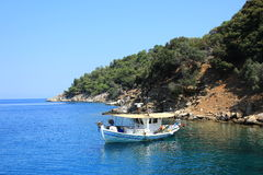 Pleasure to sail!. Boat moored on the shore of the Aegean Sea on a deserted island Stock Photo