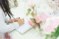 Pleasure in the wedding. Pleasure of writing a note on the address book on the wedding table Royalty Free Stock Photography