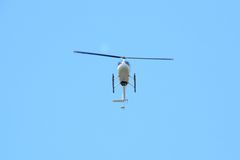 Pleasure white helicopter in flight at low altitude, front bottom view Royalty Free Stock Images