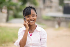 The pleasure of a young woman to call by showing a beautiful smile. This young woman is happy to call, so look at her beautiful smile Royalty Free Stock Photos