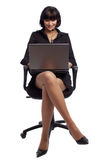 Pleasured brunette woman in dark dress. Sitting in the office chair and working on laptop over white background Royalty Free Stock Photos
