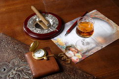 Pleasures. A glass of whiskey, wallet, and a ancient gold clock, folder of leather and cigar Royalty Free Stock Photo