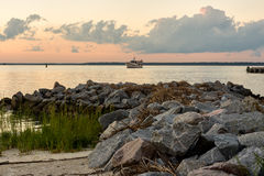 Pleasures of Hilton Head. Hilton Head Island at sunset with a boat in the bay with an outcropping of large rocks and beach Stock Photo