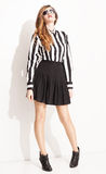 Pleated sun. Beautiful young lady with pleated skirt and striped black and white shirt posing on white background with sunglasses Stock Photography