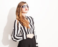 Pleated sunglasses. Beautiful model with high waisted pleated skirt wearing eyeglasses posing on white background Stock Photography