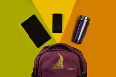 Plecak z akcesoriami, pastylka komputerem, telefonem i thermo kubkiem na jaskrawym tle, żółtej zieleni pomarańcze Strój uczeń, zdjęcie royalty free