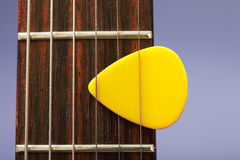 Plectrum between strings. Yellow plectrum clutched between guitar strings Royalty Free Stock Photography