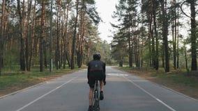 Plecy pod??a strza? dysponowany sportive cyklista w czarnego stroju je?dzieckim bicyklu Nogi z silnych mi??ni peda?uje bicyklem K zbiory