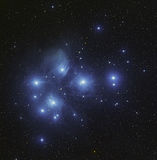 Pleiades cluster M45 in Taurus. The Pleiades or Seven Sisters (Messier 45 or M45), is an open star cluster containing middle-aged hot B-type stars located in the Stock Photo