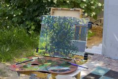 Plein air in nature. Canvas on sketchpad, a palette with used paints. Plein air in sunny landscape nature. Canvas on sketchpad, a palette with used paints Royalty Free Stock Photo