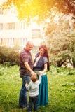 Plein-corps de famille heureuse en parc de ville au coucher du soleil Photos libres de droits