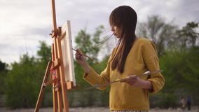Plein luftmålning Ung konstnär som arbetar på den utomhus- staffli stock video