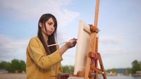 Plein luftmålning Ung konstnär som arbetar på den utomhus- staffli lager videofilmer