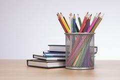 Plein panier des crayons colorés de crayon avec des livres Photo stock