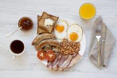 Plein petit déjeuner anglais avec les oeufs au plat, le lard, les saucisses, les haricots et les pains grillés sur le fond en boi Images libres de droits