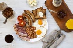 Plein petit déjeuner anglais avec les oeufs au plat, le lard, les saucisses, les haricots et les pains grillés sur le fond en boi Photos libres de droits