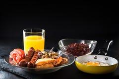 Plein petit déjeuner anglais avec les oeufs brouillés dans une poêle, un lard, une saucisse, des haricots, des tomates et un jus Image libre de droits