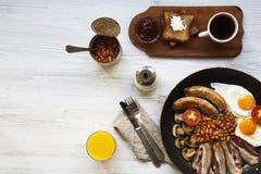 Plein petit déjeuner anglais dans une casserole avec les oeufs au plat, le lard, les haricots, les saucisses et les pains grillés Images stock