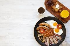 Plein petit déjeuner anglais dans une casserole avec les oeufs au plat, le lard, les saucisses, les haricots et les pains grillés Images stock