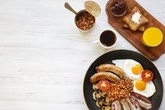 Plein petit déjeuner anglais dans une casserole avec les oeufs au plat, le lard, les saucisses, les haricots et les pains grillés Photos libres de droits