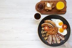 Plein petit déjeuner anglais dans une casserole avec les oeufs au plat, le lard, les saucisses, les haricots et les pains grillés Image stock