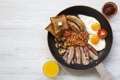 Plein petit déjeuner anglais dans une casserole avec les oeufs au plat, le lard, les saucisses, les haricots, les pains grillés e Images libres de droits