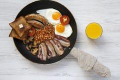 Plein petit déjeuner anglais dans une casserole avec les oeufs au plat, le lard, les saucisses, les haricots, les pains grillés e Photos libres de droits