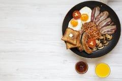 Plein petit déjeuner anglais dans une casserole avec les oeufs au plat, le lard, les saucisses, les haricots, les pains grillés e Image stock