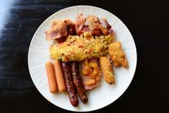 Plein petit déjeuner avec le lard de saucisse d'omelette et la pomme de terre frite Image stock