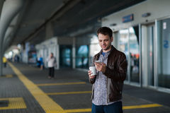 Plein portrait de corps d'un voyageur masculin marchant avec le téléphone portable et le café Image stock
