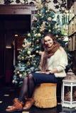 Plein portrait de corps d'une jeune belle femme de sourire s'asseyant près de l'arbre de Noël Photo stock