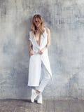 Plein portrait de manteau, de pantalons et d'espadrilles blancs de port de conception de femme de mode Image stock