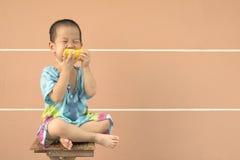 Plein portrait du garçon de l'Asie dans l'âge d'enfant en bas âge mangeant du maïs jaune Photos stock