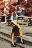 Plein portrait extérieur de corps de la jeune belle dame heureuse à la mode marchant près de l'arbre fleurissant Port modèle élég Images stock