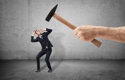 Plein-taille effrayée d'homme d'affaires dans une pose désespérée et une main géante avec un marteau threting le sur le fond gris Photo libre de droits