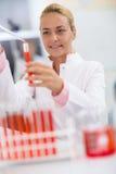 Plein tube à essai de technicien chimique féminin avec le liquide témoin Photographie stock