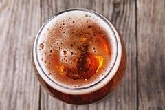 Plein verre de bière blonde sur une table en bois image stock