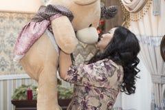 Pleine femme asiatique tenant et embrassant un grand ours de nounours Image libre de droits