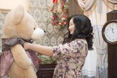 Pleine femme asiatique tenant et embrassant un grand ours de nounours Photos libres de droits
