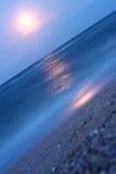 Pleine lune au-dessus d'une plage la nuit Photographie stock libre de droits