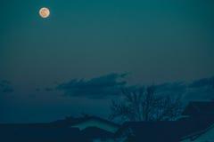 Pleine lune au-dessus des toits Photo stock