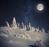 Pleine lune en ciel nocturne en montagnes d'hiver Image libre de droits