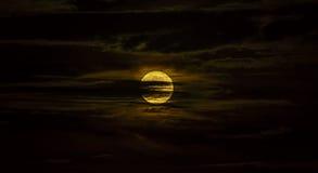 Pleine lune entourée par les nuages soyeux la nuit Photographie stock libre de droits