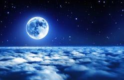Pleine lune lumineuse dans un ciel nocturne étoilé au-dessus des nuages rêveurs avec la lumière rougeoyante molle photographie stock libre de droits